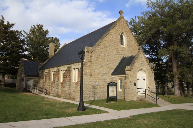 Photo of a tan stone church with black roof and double white doors. A lamp post and a sidewalk is visible in the foreground